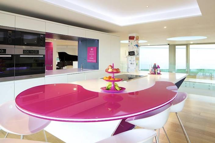 <p>Built into the house are ways to change up and extend the various spaces, like this bright kitchen island. </p>