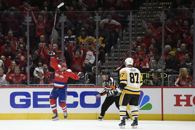 Washington Capitals left wing Jakub Vrana (13) celebrates his goal as Pittsburgh Penguins center Sidney Crosby (87) skates by during the first period of an NHL hockey game, Sunday, Feb. 23, 2020, in Washington. (AP Photo/Nick Wass)
