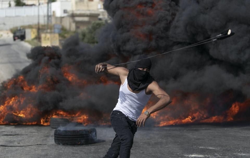 """<span class=""""caption"""">A Palestinian protester uses a slingshot during clashes with Israeli soldiers at the northern entrance of the West Bank city of Ramallah on May 21, the day a cease-fire took effect after 11 days of heavy fighting between Israel and Gaza's Hamas rulers. </span> <span class=""""attribution""""><span class=""""source"""">(AP Photo/Nasser Nasser) </span></span>"""