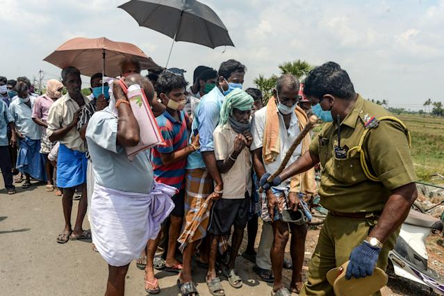 A policeman in Chennai regulates the crowd as people line up to buy alcohol after the government eased a nationwide lockdown in May. A full lockdown has been reimposed in the region following a spike on coronavirus cases (Arun Sankar/AFP)