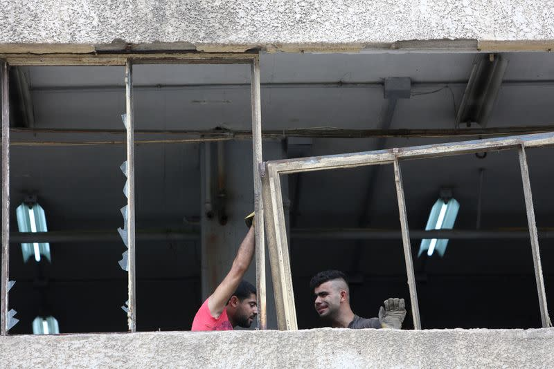Workers fix windows of Sleep Comfort furniture factory that was damaged during Beirut port blast