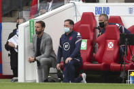 England's coach Gareth Southgate, left, along with technical staff and substitutes take a knee before the international friendly soccer match between England and Romania in Middlesbrough, England, Sunday, June 6, 2021. (AP Photo/Scott Heppell, Pool)