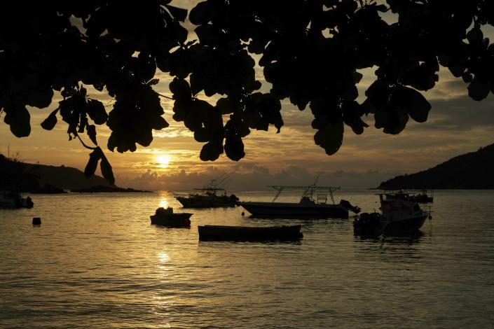 FILE - In this Friday, March 1, 2019 file photo, the sun sets over a small bay with fishing and pleasure crafts at anchor, on Mahe island, Seychelles. The president of the Indian Ocean island nation of Seychelles says he hopes enough residents will soon be vaccinated against COVID-19 to stop the spread of the virus, hoping to achieve herd immunity by mid-March 2021 by vaccinating about 70% of the population. (AP Photo/David Keyton, File)
