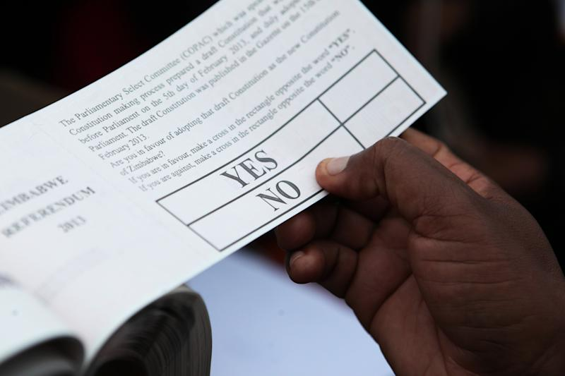 """An election official holds one of the ballot papers for use during a referendum in Harare, Zimbabwe, Saturday, March, 16, 2013. All political groups have called for a """"Yes"""" vote on a constitution whose reforms would reduce presidential powers and grant more democratic rights. However, even if the constitution is approved, arrests and harassment of rights and democracy activists this year by police loyal to Mugabe raise doubts about whether such changes would be seriously enforced. (AP Photo/Tsvangirayi Mukwazhi)"""
