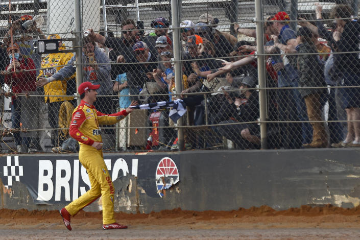 Joey Logano is handed the checkered flag after winning a NASCAR Cup Series auto race, Monday, March 29, 2021, in Bristol, Tenn. (AP Photo/Wade Payne)