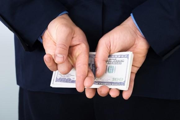A businessman in a suit holding a neat stack of hundred dollar bills behind his back and crossing his fingers.