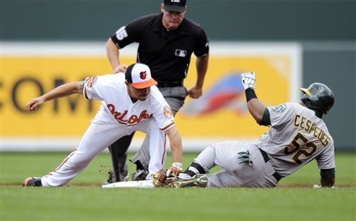 Baltimore Orioles second baseman Omar Quintanilla, left, tags out Oakland Athletics' Yoenis Cespedes (52) at second after Cespedes tried to stretch his single into a double during the second inning of a baseball game, Sunday, July 29, 2012, in Baltimore. (AP Photo/Nick Wass)