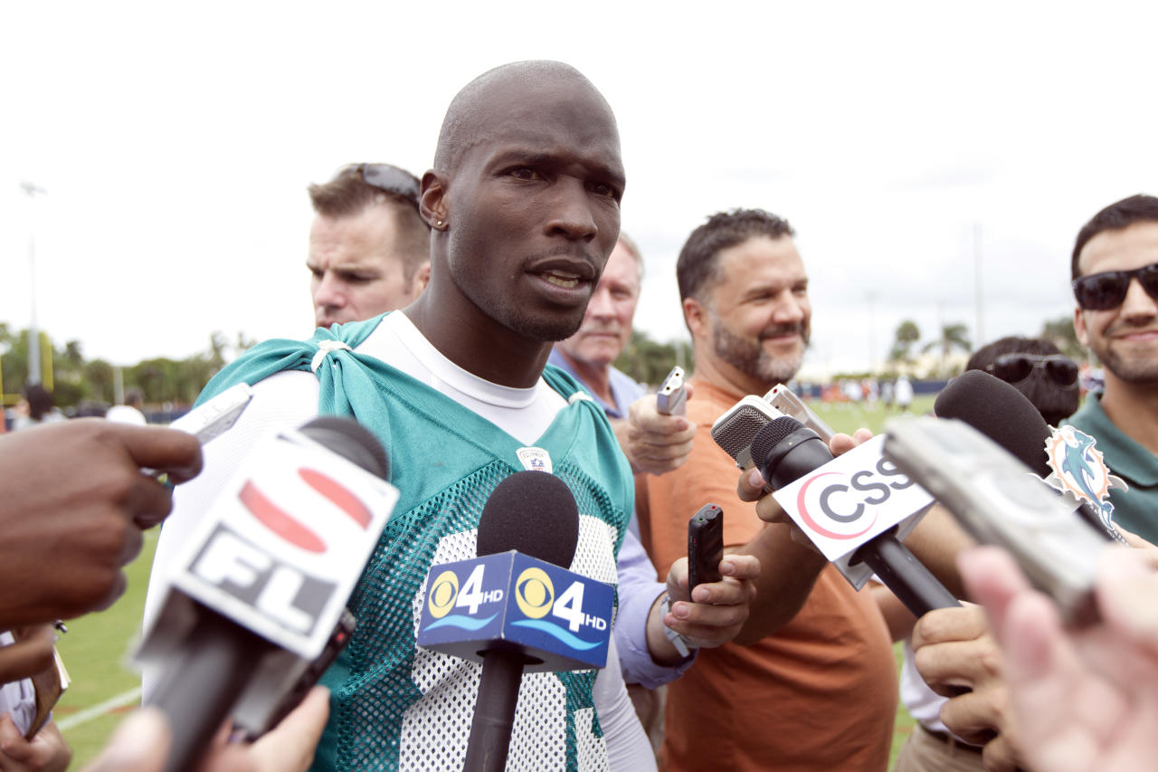 FILE - This June 19, 2012 file photo shows Miami Dolphins player Chad Ochocinco, who recently changed his name back to Chad Johnson, talking to the media after NFL practice in Davie, Fla. The Dolphins terminated the six-time Pro Bowl receiver's contract about 24 hours after he was arrested in a domestic battery case involving his wife. Johnson was released from jail on $2,500 bond earlier Sunday, Aug. 12, 2012, after his wife accused him of head-butting her during an argument in front of their home. (AP Photo/J Pat Carter, File)