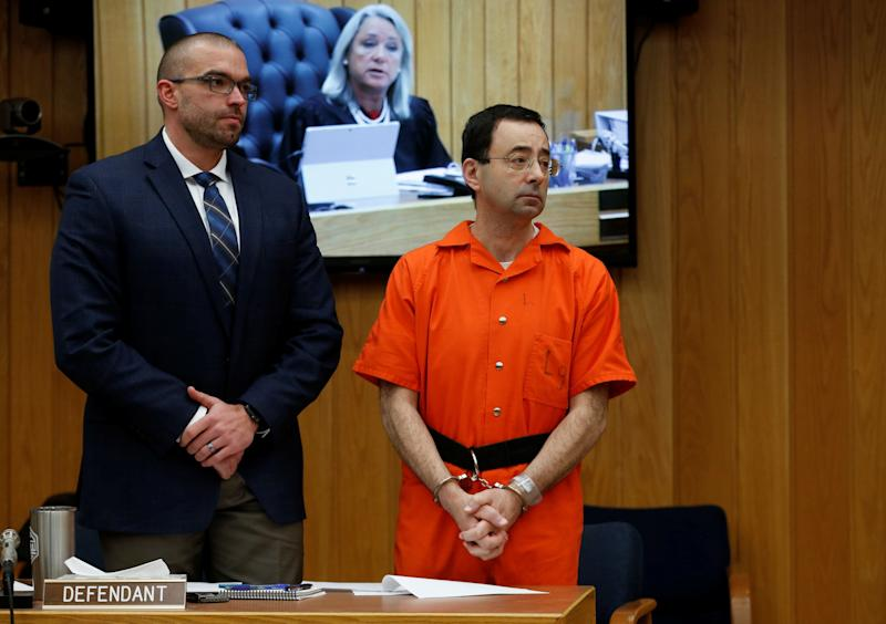 Larry Nassar stands with his attorney Matt Newburg as Judge Janice Cunningham (seen on screen) gives instructions during Nassar's second sentencing in the Eaton County Circuit Court in Charlotte, Michigan, U.S., January 31, 2018.
