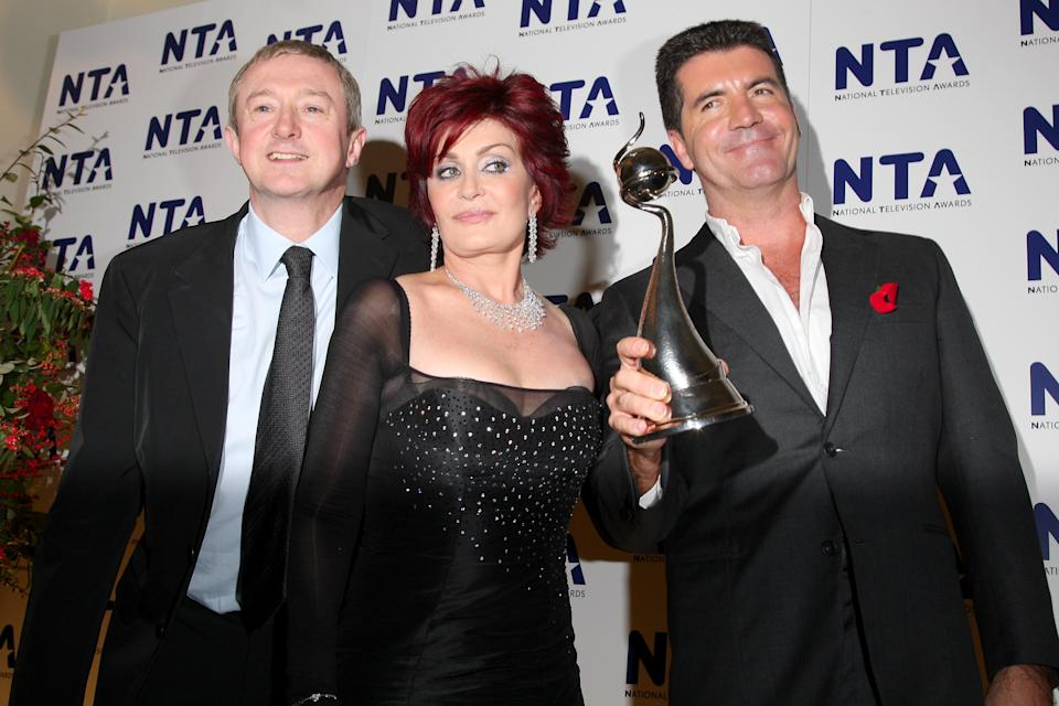 """LONDON - OCTOBER 31:  Members of the """"The X Factor"""" Louis Walshe, Sharon Osbourne and Simon Cowell pose with the award for Most Popular Talent Show at the National Television Awards 2007 held at the Royal Albert Hall on October 31, 2007 in London, England.  (Photo by Jon Furniss/WireImage)"""