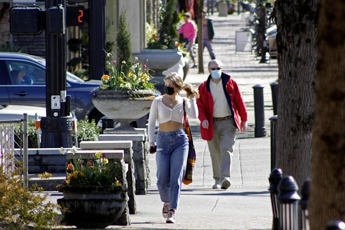 Residents wearing masks walk in downtown Lake Oswego, Ore., on Sunday. Tens of thousands of Oregon residents are angry about a proposal to make permanent an emergency rule that requires masks and social distancing in the state's businesses and schools to prevent the spread of COVID-19.