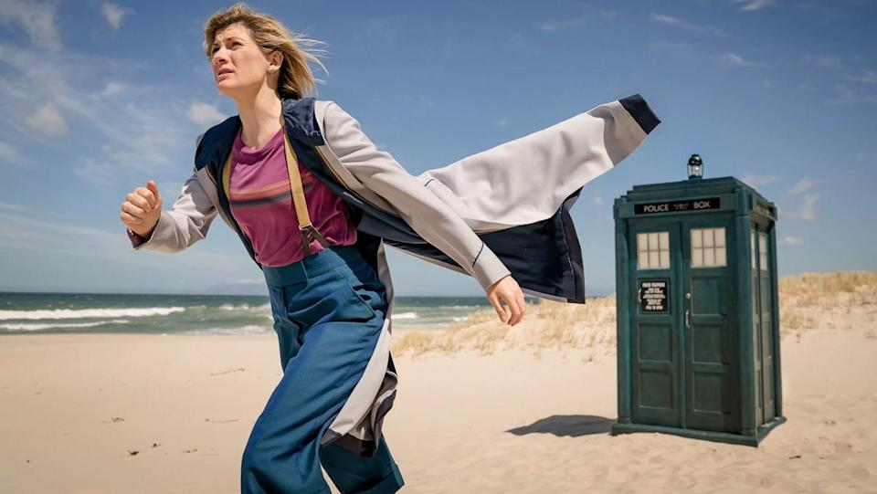Jodie Whittaker in her usual Thirteenth Doctor costume of high-waisted trousers, suspenders, a t-shirt, and a long raincoat, walks away from the TARDIS on a sunny beach near a body of water.