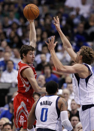 Houston Rockets' Goran Dragic, left, of Slovenia, passes as Dallas Mavericks' Shawn Marion (0) and Dirk Nowitzki, right, defend in the first half of an NBA basketball game on Wednesday, April 18, 2012, in Dallas. (AP Photo/Tony Gutierrez)