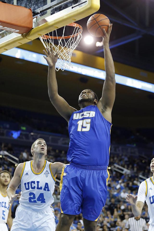 UC Santa Barbara's Alan Williams, right, scores in front of UCLA's Travis Wear, left, during the first half of an NCAA college basketball game, Tuesday, Dec. 3, 2013, in Los Angeles. (AP Photo/Danny Moloshok)