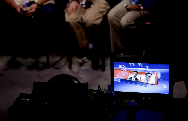 A screen displays photos of Republican presidential candidate, former Massachusetts Gov. Mitt Romney, right, and President Barack Obama, as a television news crew prepares on Monday, Oct. 15, 2012, for Tuesday's presidential debate at Hofstra University in Hempstead, N.Y. (AP Photo/David Goldman)