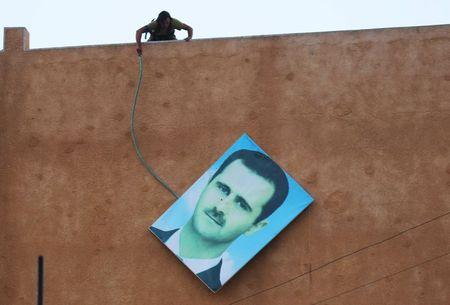 A member of al Qaeda's Nusra Front takes down a picture of Syria's President Bashar al-Assad in the northwestern city of Ariha, after a coalition of insurgent groups seized the area in Idlib province May 29, 2015.  REUTERS/Ammar Abdullah