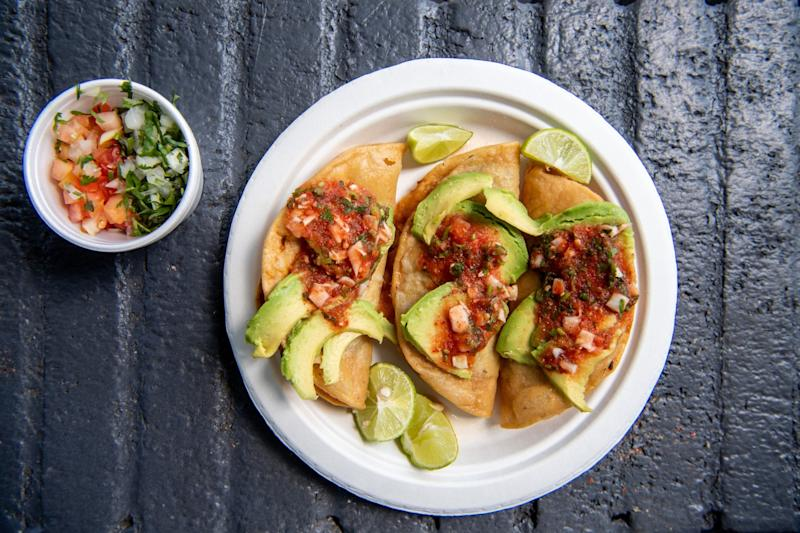 Mariscos Jalisco's tacos dorados de camaron on a plate with lime wedges and avocado slices.