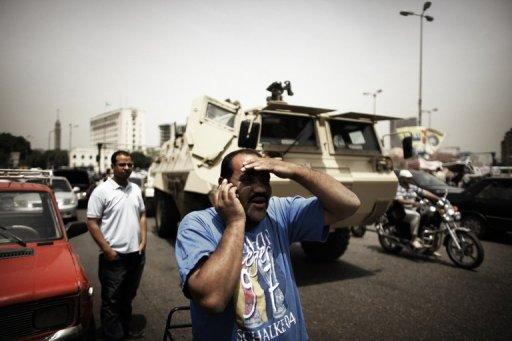 An Egyptian man talks on the telephone in front of an army vehicle in central Cairo's Tahrir Square in May 2012