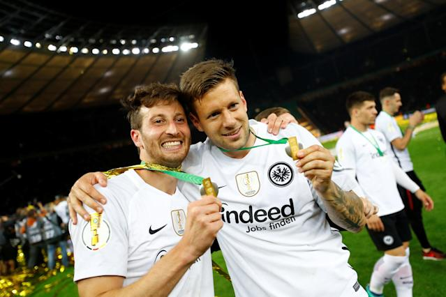 Soccer Football - DFB Cup Final - Bayern Munich vs Eintracht Frankfurt - Olympiastadion, Berlin, Germany - May 19, 2018 Eintracht Frankfurt's Marco Russ and David Abraham celebrate with their medals after winning the DFB Cup REUTERS/Kai Pfaffenbach DFB RULES PROHIBIT USE IN MMS SERVICES VIA HANDHELD DEVICES UNTIL TWO HOURS AFTER A MATCH AND ANY USAGE ON INTERNET OR ONLINE MEDIA SIMULATING VIDEO FOOTAGE DURING THE MATCH.