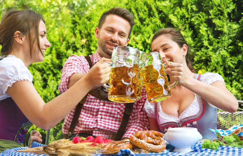 Young people in Tracht, Dindl and Lederhosen having fun in Beer garden in Bavaria, Germany