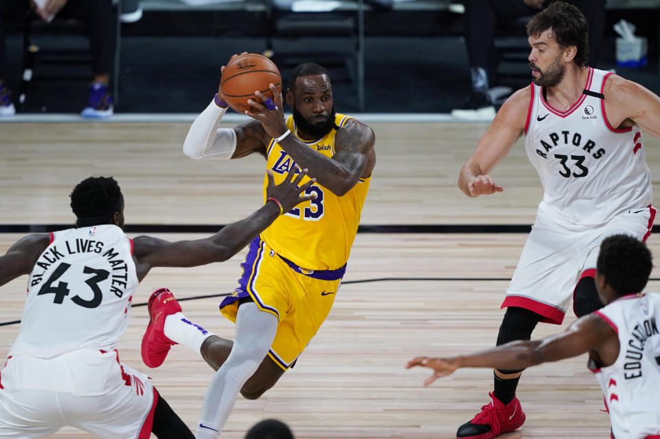 Los Angeles Lakers' LeBron James (23) drives around Toronto Raptors' Pascal Siakam (43) and Marc Gasol (33) during the first half of an NBA basketball game Saturday, Aug. 1, 2020, in Lake Buena Vista, Fla. (AP Photo/Ashley Landis, Pool)