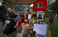 Women's rights activists place candles and flowers beside posters with the pictures of Noor Mukadam, who was recently beheaded, during a candle light vigil to pay tribute to Noor and other domestic violence victims in Islamabad, Pakistan, Sunday, July 25, 2021. The killing of Mukadam in an upscale neighborhood of Pakistan's capital has shone a spotlight on the relentless violence against women in the country. Rights activists say such gender-based assaults are on the rise as Pakistan barrels toward greater religious extremism. (AP Photo/Anjum Naveed)