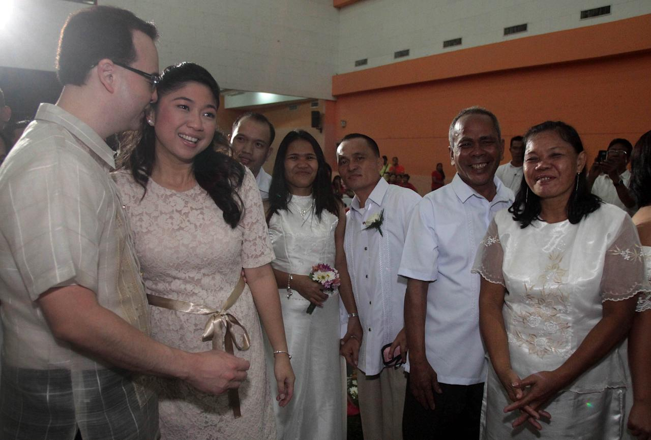 <p>Senator Alan Peter Cayetano and wife Taguig Mayor Maria Laarni Cayetano join couples at a mass wedding in Taguig City, Feb. 14, 2013. (George Calvelo, NPPA Images)</p>
