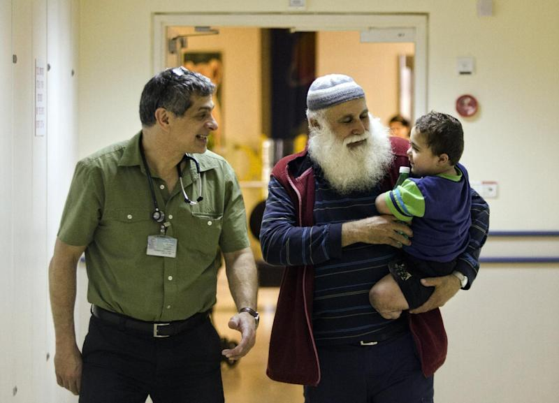 "In this Monday, April 29, 2013 photo, Palestinian Hamouda Al-Farra, holds his grandson Mohammed as they speak with Israeli doctor Raz Somech, in the Tel Hashomer Hospital near Ramat Gan, central Israel. Abandonment, generosity and tragedy have each shaken Mohammed al-Farra's life since he was born in the southern Gaza Strip town of Khan Younis three and a half years ago with a rare genetic disorder that crippled his bowels, weakened his immune system and caused an infection that destroyed his hands and feet. His parents abandoned him and the Palestinian government won't pay for his care. But his grandfather has raised him instead, and Israeli doctors privately fundraise to cover his medical costs. As a result, the Palestinian toddler calls his grandfather ""daddy,"" he babbles in a mix of Hebrew and Arabic and the only home he has ever known is the yellow-painted children's ward. (AP Photo/Dan Balilty)"