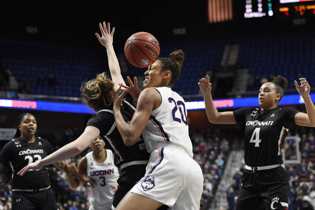 Connecticut's Olivia Nelson-Ododa, center right, is fouled by Cincinnati's Sam Rodgers, center left, during the first half of an NCAA college basketball game in the American Athletic Conference tournament finals at Mohegan Sun Arena, Monday, March 9, 2020, in Uncasville, Conn. (AP Photo/Jessica Hill)