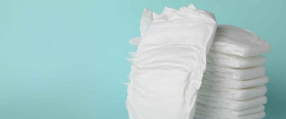 Stack of diapers on light blue background. Space for text