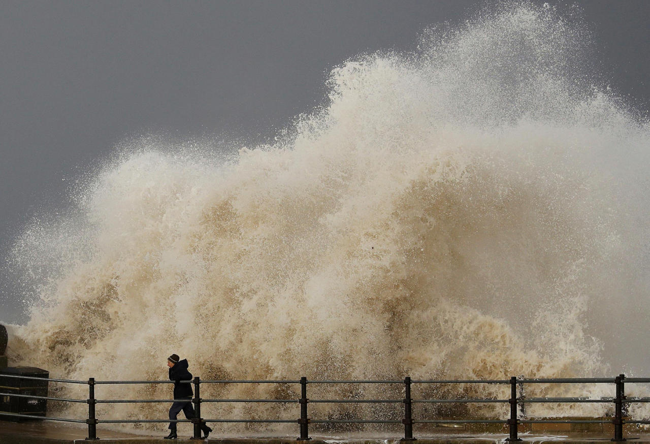 <p>A woman is battered by a wave as he walks along the seafront in New Brighton, northern England Nov. 16, 2016. (Photo: Phil Noble/Reuters) </p>