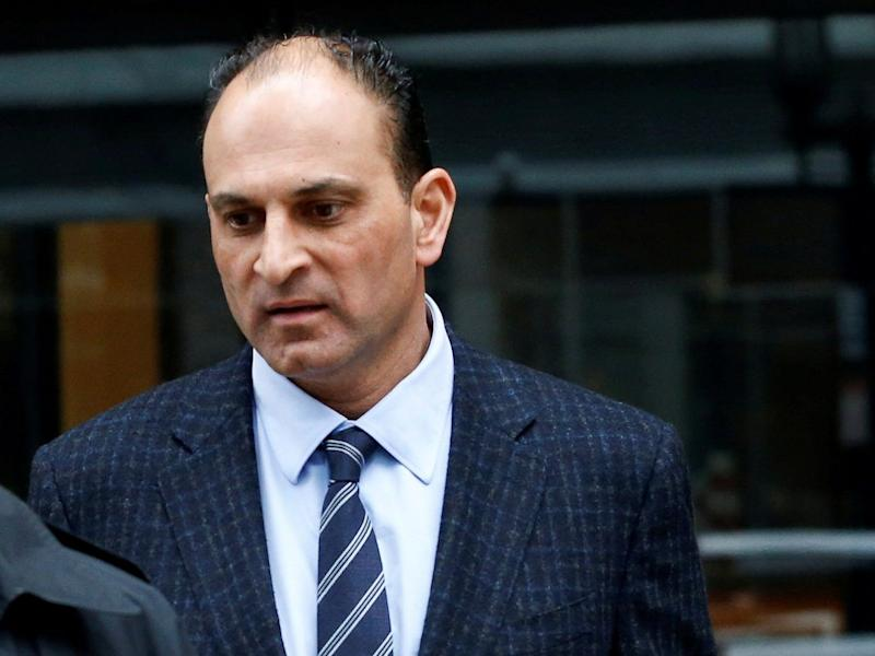 David Sidoo (R), a Vancouver businessman and former Canadian Football League player, leaves the federal courthouse after entering a plea in connection with a nationwide college admissions cheating scheme in Boston, Massachusetts, U.S., March 13, 2020.