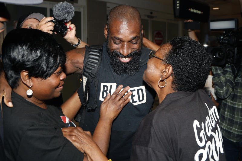 Wendell Brown hugs relatives after his arrival at the Detroit Metropolitan Airport, Wednesday, Sept. 25, 2019, in Romulus, Mich. Brown returned from China where he was imprisoned for his involvement in a bar fight. Brown, a native of Detroit had been teaching English and American football in southwest China when he was arrested in September 2016 and charged with intentional assault. (AP Photo/Carlos Osorio)
