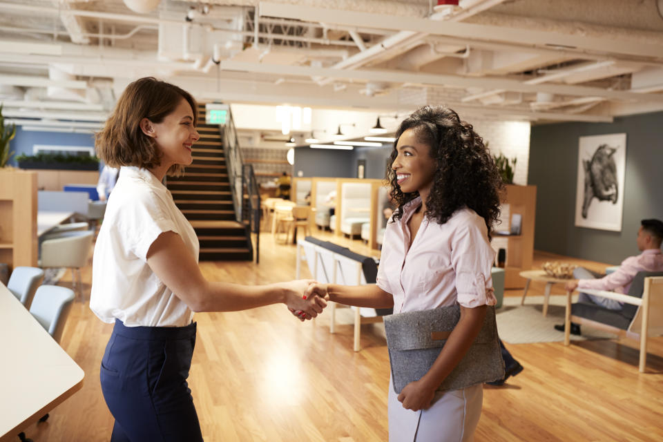 Two Businesswomen Meeting And Shaking Hands In Modern Open Plan Office