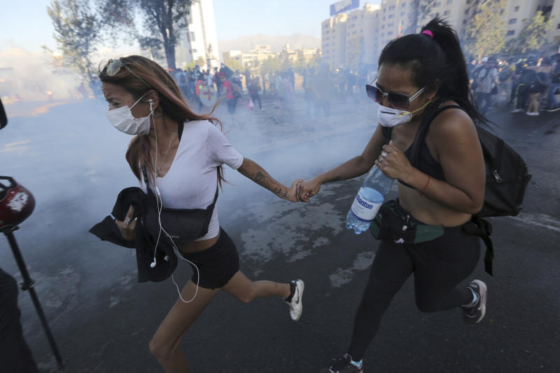 Anti-government demonstrators run away from a cloud of teargas during clashes with the police in Santiago, Chile, Friday, December 20, 2019. Chile is a celebrating second full month of unprecedented social revolt that has not only altered the country's political landscape, but has also pushed a referendum on the reform of the country's dictatorship. (AP Photo/Fernando Llano)
