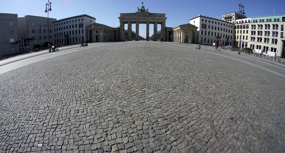 Only a few people visit the square in front of the Brandenburg Gate in Berlin, Germany, Tuesday, March 24, 2020. In order to slow down the spread of the coronavirus, the German government has considerably restricted public life and asked the citizens to stay at home and keep distance from other people. (AP Photo/Michael Sohn)