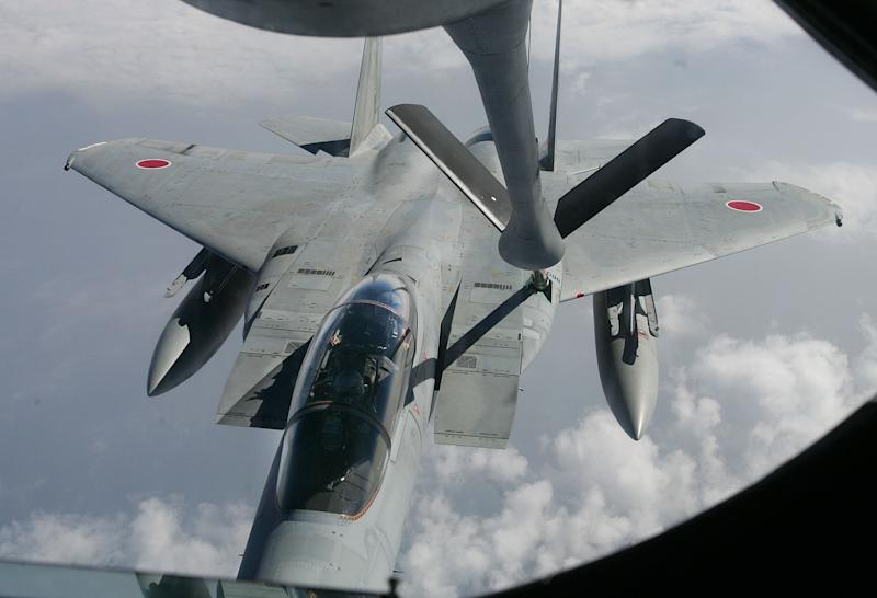 FILE - In this Thursday, April. 21, 2005 file photo, Japan Air Self Defense Force F-15DJ fighter hooks up a boom as it receives a mid-air refueling from a KC-135R Tanker of U.S. Airforce 909th Air Refuelling Squadron, based in Kadena Air Base in Okinawa, Southern Japan, during a Joint U.S. and Japan air refueling training over the East China Sea. Japan on Tuesday, Dec. 17, 2013, approved a plan to increase defense spending by 5 percent over the next five years to purchase its first surveillance drones, more jet fighters and naval destroyers in the face of China's military expansion. (AP Photo/Itsuo Inouye, File)