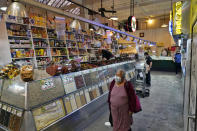 A woman walks past a shop at the Grand Central Market, Monday, Nov. 16, 2020, in Los Angeles. Gov. Gavin Newsom announced Monday, Nov. 16, 2020, that due to the rise of COVID-19 cases, some counties have been moved to the state's most restrictive set of rules. The new rules begin Tuesday, Nov. 17. (AP Photo/Marcio Jose Sanchez)
