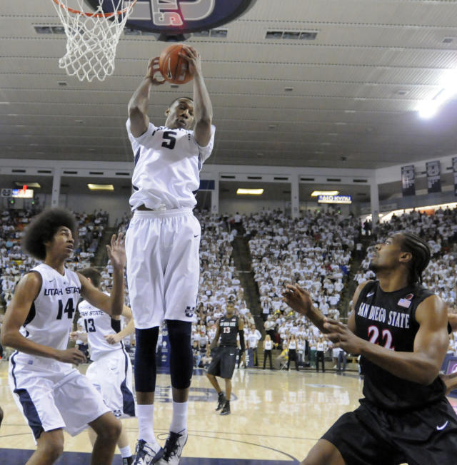 Utah State center Jarred Shaw (5) grabs a rebound over teammate Jalen Moore (14) and San Diego State forward Josh Davis (22) during the first half of an NCAA college basketball game Saturday, Jan. 25, 2014, in Logan, Utah. (AP Photo/Eli Lucero)