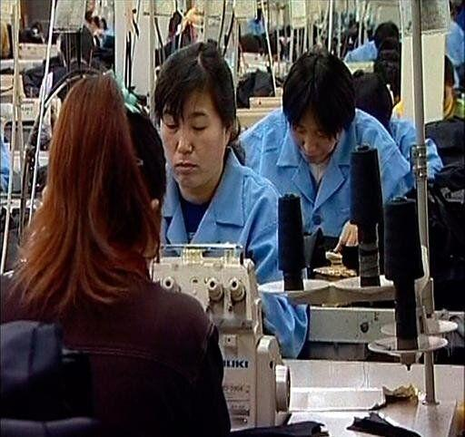 Wholesale garment factory workes at sewing machines, Beijing, China, video still