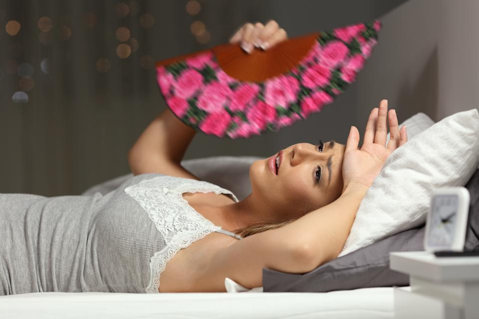Overwhelmed woman faning suffering heat stroke lying in the bed in the night at home