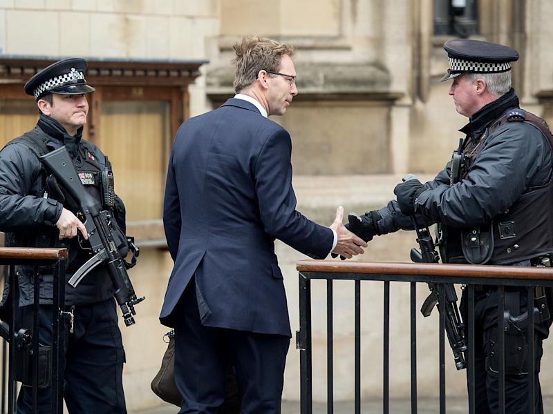Tobias Ellwood MP shakes hands with an armed policeman as he arrives at the Houses of Parliament: Getty Images