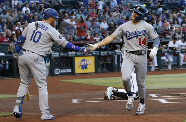 Los Angeles Dodgers' Enrique Hernandez (14) celebrates his home run against the Arizona Diamondbacks with Dodgers' Justin Turner (10) during the first inning of a baseball game, Tuesday, June 25, 2019, in Phoenix. (AP Photo/Ross D. Franklin)
