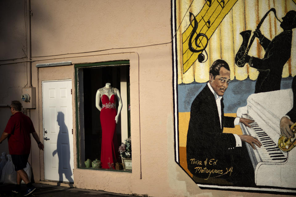 """An evening gown is displayed in a store window next to a mural titled """"Harlem Nights in Palatka,"""" featuring musicians from the town that formed a 1920s jazz band, as a pedestrian walks by in downtown Palatka, Fla., on Tuesday, April 13, 2021. (AP Photo/David Goldman)"""