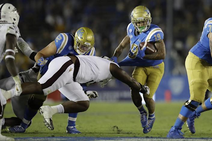 UCLA running back Kazmeir Allen has his jersey pulled as a defender dives toward his legs while he runs with the ball.