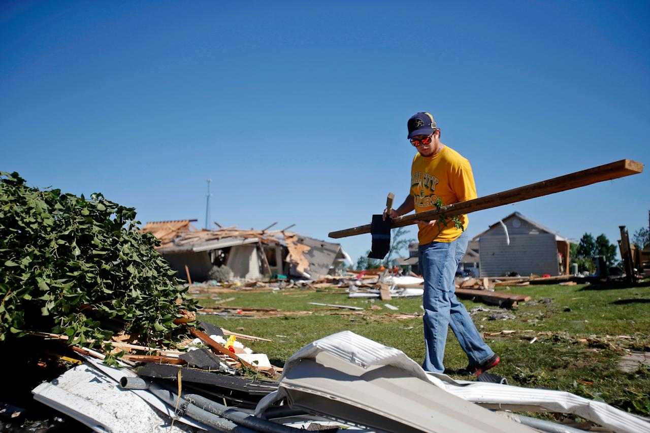 Alex Wills of Mazon helps his uncle clean up his property on W. Daisy Place on June 23, 2015 after a tornado struck the previous day in Coal City, Illinois. The National Weather Service has confirmed that at least five tornadoes touched down in north central Illinois, causing widespread damage and power outages. (Photo by Jon Durr/Getty Images)