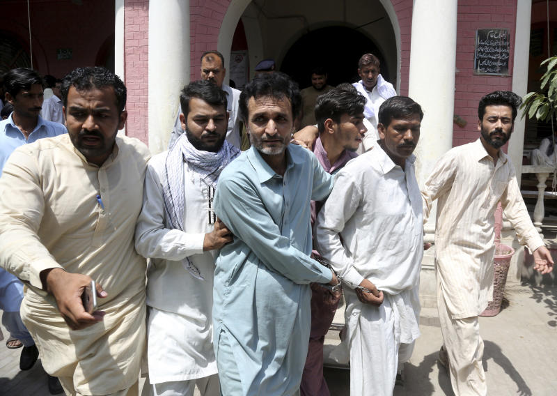 In this May 15, 2019, photo, officials of Pakistan's Federal Investigation Agency escort detain criminals allegedly involved in a trafficking gang to lure Pakistani women into fake marriages, to a court in Faisalabad, Pakistan. (AP Photo/K.M. Chaudary)
