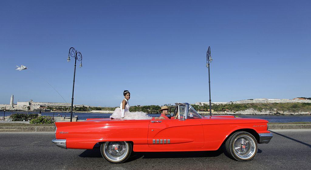 <p>Carmen Gonzalez rides in the back of a vintage car during a photo session in the old quarters of Havana as part of her quinceanera.</p>