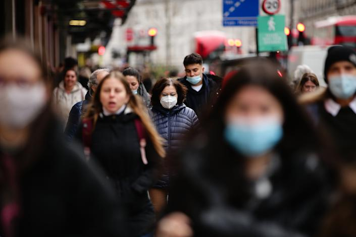 A woman wearing a face mask walks amid shoppers on Regent Street in London, England, on December 4, 2020. London has returned to so-called Tier 2 or 'high alert' coronavirus restrictions since the end of the four-week, England-wide lockdown on Wednesday, meaning a reopening of non-essential shops and hospitality businesses as the festive season gets underway. Rules under all three of England's tiers have been strengthened from before the November lockdown, however, with pubs and restaurants most severely impacted. In London's West End, Oxford Street and Regent Street were both busy with Christmas shoppers this afternoon, meanwhile, with the retail sector hoping for a strong end to one of its most difficult years. (Photo by David Cliff/NurPhoto via Getty Images)