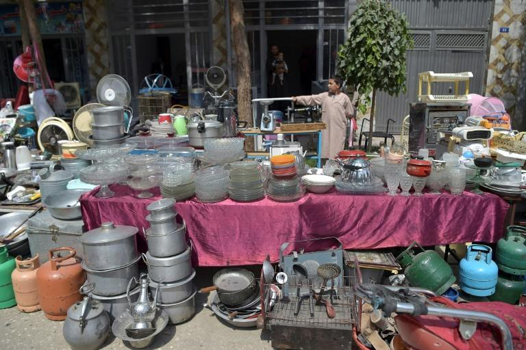A young shopkeeper offers household items for sale at a market in Kabul (AFP/WAKIL KOHSAR)